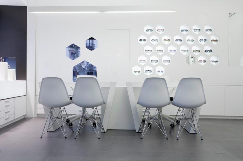 Mesas, sillas y expositor en el interior de Óptica Lancis